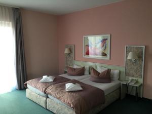 A bed or beds in a room at AltstadtHotel an der Werra