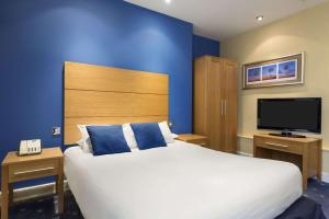A bed or beds in a room at Ramada Loughborough Hotel