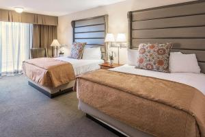 A bed or beds in a room at Westmark Anchorage Hotel