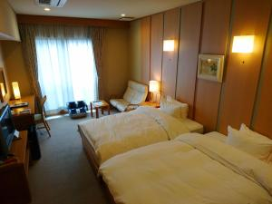 A bed or beds in a room at Kasuga Hotel