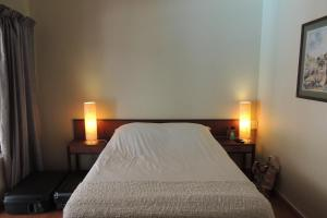 A bed or beds in a room at Brackens Guest House