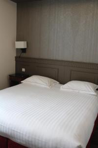 A bed or beds in a room at Best Western Plus Hôtel D'Angleterre