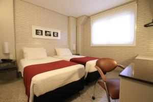 A bed or beds in a room at Hotel Confiance Soho Batel
