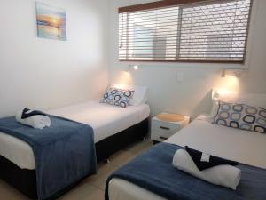 A bed or beds in a room at Cranbourne Court Unit 7