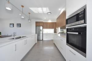 A kitchen or kitchenette at Luxury Home Mermaid Waters with Lake View