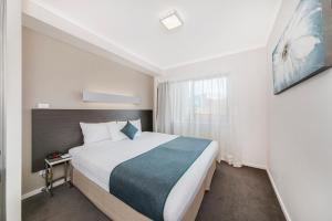 A bed or beds in a room at Abode Tuggeranong