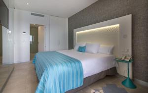 A bed or beds in a room at Suitopía - Sol y Mar Suites Hotel