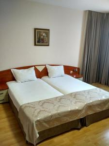 A bed or beds in a room at Philippopolis Hotel