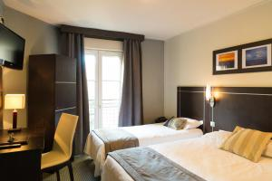 A bed or beds in a room at Hôtel Le Home Saint Louis