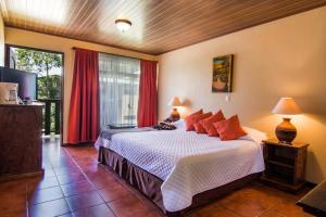 A bed or beds in a room at Monteverde Country Lodge - Costa Rica
