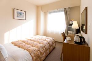 A bed or beds in a room at Hotel Keifuku Fukui Ekimae
