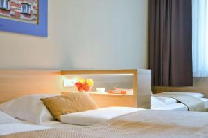 A bed or beds in a room at Ahotel Ljubljana