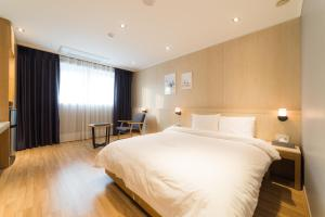 A bed or beds in a room at Reborn Suwon Silkroad Hotel