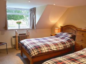 A bed or beds in a room at Longcroft Cottage