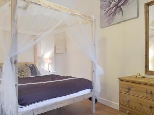 A bed or beds in a room at Dairy Cottage