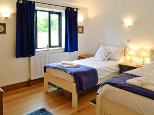 A bed or beds in a room at Woodpecker Cottage