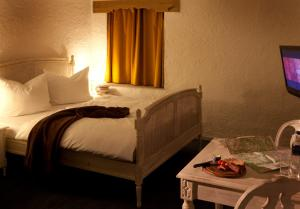 A bed or beds in a room at Hotel Hüttenmühle Hillscheid