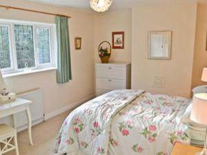 A bed or beds in a room at Heather Cottage