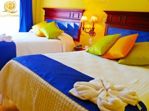A bed or beds in a room at Hotel Las Hamacas