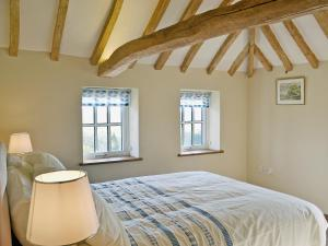 A bed or beds in a room at Honeypot Cottage