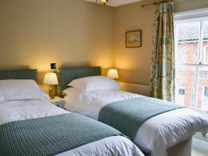 A bed or beds in a room at Pippin Cottage