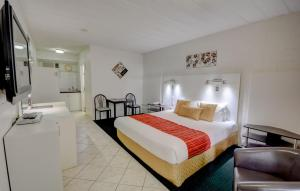 A bed or beds in a room at Elkira Court Motel