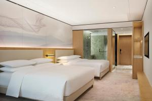 A bed or beds in a room at Four Points by Sheraton Changsha, Meixi Lake