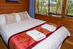 A bed or beds in a room at Snowy River Cabins