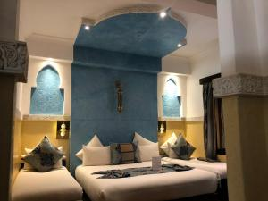 A bed or beds in a room at Riad Nesma Suites & Spa