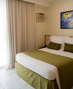 A bed or beds in a room at Bristol Guarapari Residence