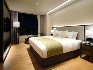 A bed or beds in a room at Grand Mercure Ambassador Hotel and Residences Seoul Yongsan