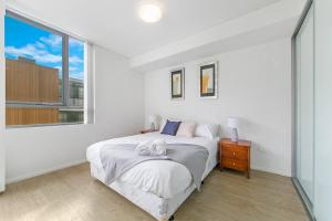 A bed or beds in a room at 2Bed Apt in Macquarie Park Walk Station NNR306