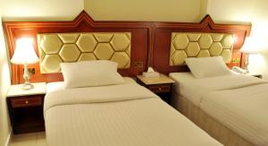 A bed or beds in a room at Saffron Hotel