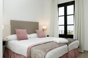 A bed or beds in a room at Suites La Posada De Pilar
