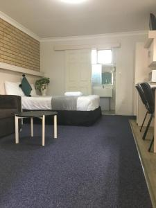 A bed or beds in a room at Jolly Swagman Motor Inn