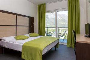 A bed or beds in a room at Panoramic Hotel Benacus