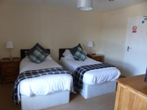 A bed or beds in a room at Acorn Guest House