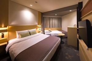 A bed or beds in a room at Nagoya Sakae Tokyu REI Hotel
