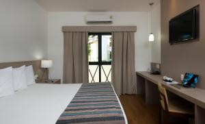 A bed or beds in a room at Flamboyant Hotel & Convention