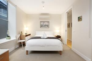 A bed or beds in a room at StayCentral Merigold on Collins