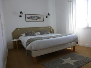 A bed or beds in a room at Hotel La Licorne