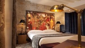 A bed or beds in a room at Hotel Le Notre Dame Saint Michel