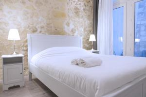 A bed or beds in a room at Ausone Beautiful loft apartment in historical center + terrace and parking