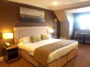 A bed or beds in a room at Fairfield House Hotel