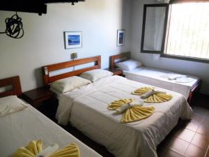 A bed or beds in a room at Pousada Manobra