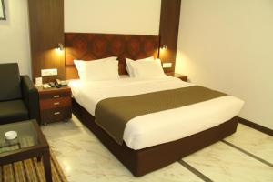 A bed or beds in a room at Amantra Comfort Hotel
