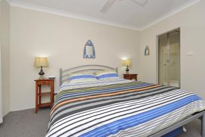 A bed or beds in a room at Cottage Court 10 - Nelson Bay