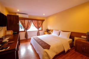 A bed or beds in a room at Crown Prince Hotel