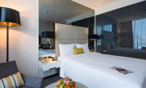 A bed or beds in a room at Centro Westside by Rotana