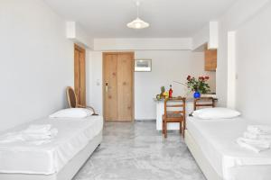 A bed or beds in a room at Artemis Hotel Apartments